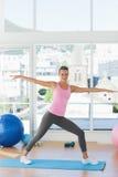 Sporty молодая женщина протягивая руки в студии фитнеса Стоковые Фото