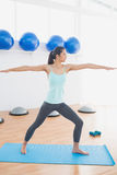 Sporty молодая женщина протягивая руки в студии фитнеса Стоковые Изображения RF
