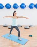 Sporty молодая женщина протягивая руки в студии фитнеса Стоковое Изображение