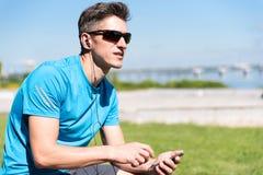 Sporty парень слушая к музыке пока тренирующ Стоковые Изображения