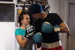Sporty пары в перчатках бокса стоя близко груша бокса стоковое фото rf