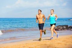 Sporty пары jogging совместно на пляже Стоковые Изображения