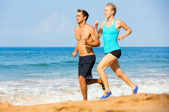 Sporty пары jogging совместно на пляже Стоковая Фотография RF