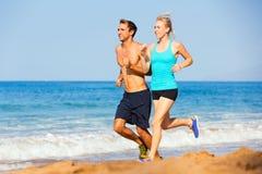 Sporty пары jogging совместно на пляже Стоковое Изображение