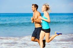 Sporty пары jogging совместно на пляже Стоковое Фото