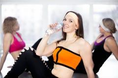 Sporty питьевая вода девушки после практики спорта в спортзале Стоковая Фотография RF