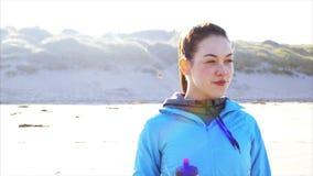 Sporty питьевая вода женщины на пляже после бега акции видеоматериалы