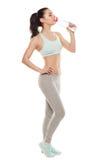 Sporty питьевая вода от бутылки после разминки, тренировка девушки фитнеса, изолированная на белой предпосылке Стоковые Фотографии RF