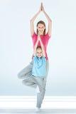 Sporty представление йоги дерева матери и дочери практикуя и mudra namaste совместно Стоковые Фотографии RF