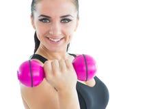 Sporty привлекательная женщина усмехаясь на камере пока тренирующ с розовой гантелью Стоковая Фотография RF