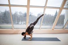 Sporty разработка женщины, делая asana йоги handstand руки балансируя, одно шагающее представление крана, половинное представлени Стоковое Изображение