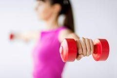Sporty руки женщины с светлыми красными гантелями стоковые фотографии rf