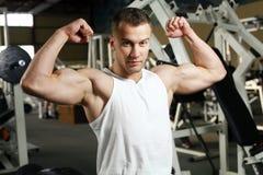 Sporty сексуальный человек представляя в спортзале Стоковые Фото