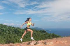 Sporty след девушки бежать на скалистом пути дня горы солнечного Стоковое Изображение RF