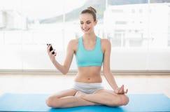 Sporty усмехаясь женщина держа smartphone стоковая фотография