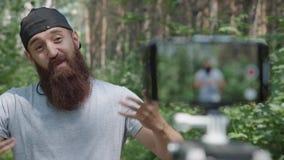 Sporty человек в серой футболке и с бородой записывает видео- блог сток-видео
