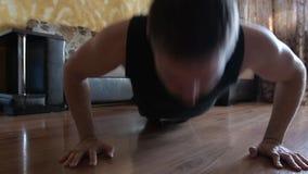 Sporty человек делая тренировку нажима-вверх дома сток-видео