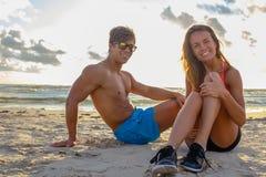 Sporty человек и женщина ослабляя на пляже Стоковая Фотография RF