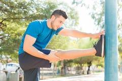 Sporty человек протягивая ногу и руку на поляке в парке стоковая фотография rf