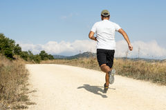 Sporty человек бежать вниз с песочного следа. стоковая фотография