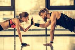 Sporty человек и женщина делая тренировку планки и давая максимум 5 Стоковые Фотографии RF