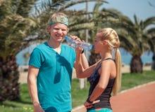 2 sporty люд выпивают воду после внешней тренировки Стоковое Фото