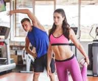 2 sporty люд делая протягивать на спортзале Стоковые Изображения RF