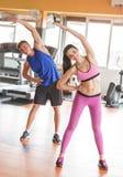 2 sporty люд делая протягивать на спортзале Стоковая Фотография RF