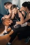 Sporty люди и женщины сидя на стенде в спортзале Стоковые Фотографии RF