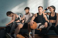 Sporty люди и женщины сидя на стенде в спортзале Стоковые Изображения RF