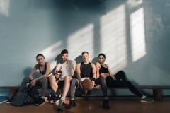 Sporty люди и женщины сидя на стенде в спортзале Стоковая Фотография RF