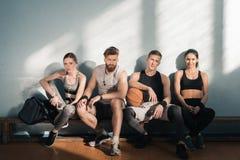 Sporty люди и женщины сидя на стенде в спортзале Стоковое Изображение