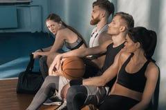 Sporty люди и женщины сидя на стенде в спортзале Стоковое Фото