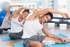 Sporty люди протягивая руки на занятиях йогой Стоковое Фото