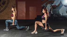 2 маленькой девочки красивых фитнеса sporty делая выпады с гантелями в спортзале стоковые изображения rf