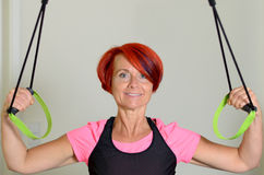 Sporty Adult Woman Pulling Down a Resistance Band Royalty Free Stock Image