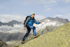 Sporty alpinist взбирается саммит горы в швейцарских Альпах Стоковые Фото