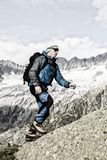 A sporty alpinist climbs a mountain summit in the Swiss Alps. Goeschenen Stock Images