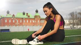 Sporty asian girl in sportswear is tying shoelaces on sneakers sitting on the stadium before training. Sporty asian girl in sportswear is tying shoelaces on stock video