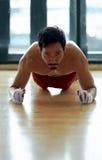 Sporty asian man doing push ups exercise Stock Image