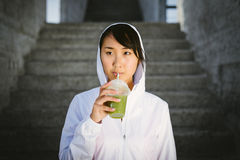 Sporty asian woman drinking smoothie detox Stock Photo