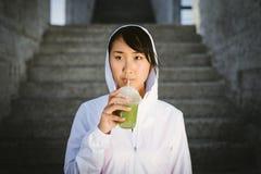 Sporty asian woman drinking smoothie detox stock photo