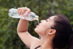 Sporty Asian woman drinking water. Stock Images