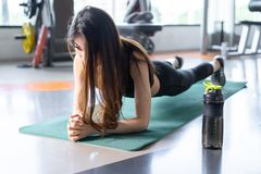 Sporty asian woman exercise doing plank at gym. Workout fitness, female athlete muscle building strong healthy lifestyle with protein shake bottle stock photos