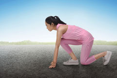 Sporty asian woman fit in ready position to running exercise. In concrete track Royalty Free Stock Image