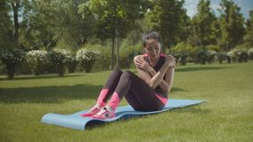 Fit woman training abs on sports mat in city park stock video footage