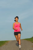 Sporty asian woman running at park. Sporty young woman running at park. Female asian athlete training outdoor Royalty Free Stock Image