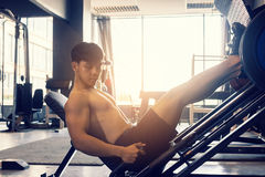 Sporty asian young man work out heavy work on leg press machine stock images
