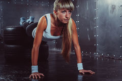 Sporty athlete woman doing push ups on tire Royalty Free Stock Images