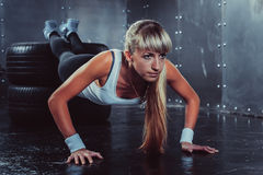 Sporty athlete woman doing push ups on tire Royalty Free Stock Photo